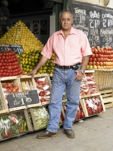 Man Standing by Fruit Kiosk